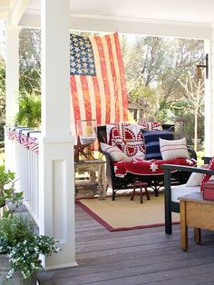 Wrapped in red, white, and blue linens, a cozy porch is just the place to pass a hot summer evening with a cool glass of lemonade. The oversize American flag makes the perfect backdrop to this patriotic setting.