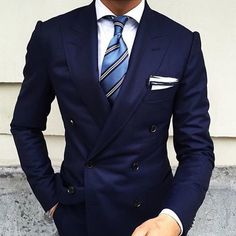 Team a navy blue double breasted blazer with a white classic shirt for a classic and refined silhouette. Shop this look on Lookastic: https://lookastic.com/men/looks/navy-double-breasted-blazer-white-dress-shirt-blue-tie/21235 — White Dress Shirt — Blue Vertical Striped Tie — White Pocket Square — Navy Double Breasted Blazer