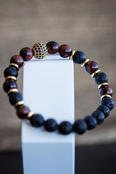 The Royal Lava Bracelet Beautiful gold coloured metal intermingled with smouldering black lava and red tiger's eye beads. This hot and fiery piece of wrist jewellery is styling yet oh so practica