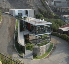 """Residential Architecture: Mirador House by 2.8x Architects: """"..The project consists of two volumes that contrast each other. A fully transparent volume predominantly glass and metal houses the social housing area allowing a clear view over the city. A second volume contains the most secretive private area of the house. The stone and concrete help to create the counterpart and to demonstrate how the building sits on the hill in a firm transparent allowing the volume to feel like a…"""