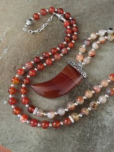 Beautiful long agate gemstone beaded necklace with horn pendant This necklace is designed with 8mm agate beads accented with silver-plated spacers. The necklace is also adorned with a short 2-1/2 link chain. The necklace is approximately 36 long and the horn pendant drops an additional
