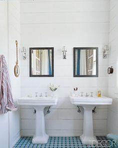 checkerboard tile flooring, wood paneled walls, and pedestal sinks.  Steven Gambrel.