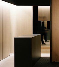 Tribeca Aoyama hair salon. Soft wood walls + black sculptural volumes + black ceiling.