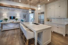 Beautiful cottage kitchen with white cabinets wood floors and marble counters