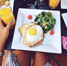 .eggs on wholemeal toast with spinach and tomatoes and fresh juice.