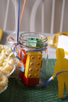 Blocks in jars for decoration or a balloon weight (if you'll have balloons), a lego guys paper chain and the table runner is just spray-painted bubble wrap to look like the lego building plates.