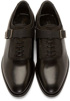 Polished leather oxfords in black. Almond toe. Coated lace-up closure. Gunmetal-tone hardware at matte black monk-strap and harness detail. Textured leather panelling at vamp, tongue, collar, and heel counter. Stacked leather heel and sole. Tonal stitching.