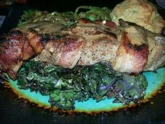 Bacon wrapped top sirloin on wilted organic purple kale.  Asparagus topped with Paleo pan gravy and a Paleo biscuit. Country Cavegirl Paleo Cuisine.