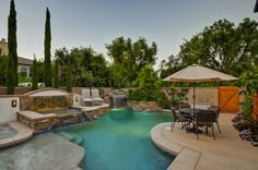 This angle focuses the perspective of the inground pool, pool waterfall. and backyard patio furniture.   Great ideas for a new modern backyard and pool can come from this image. From layouts and landscape to DIY decor style ideas.