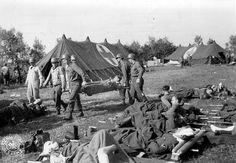Le 42nd Field Hospital US de Sainte Mère Eglise, des blessés au premier plan allongés en plein air sur des civières (le second blessé est un Gefreiter allemand).