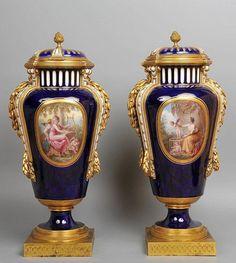 Importante paire de vases couverts, en porcelaine de Sèvres, à décor de cartouches animés d'amours musiciens ou fleuris, sur fond bleu.