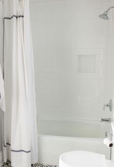 Transitional Farmhouse Hall Bath #hallbath #hall #bath #bathroom #accenttiles #tiles #wallsconce #greenery #shower #showercurtain #whitetiles #mirror #cabinets #shaker #greenandgrey #towel #silverfaucet #darkhardware #rug #decor #toiletpaperholder #towelrack    #interiordesigner #saralynnbrennan #interiors #saralynnbrennaninteriors #interiordesign #waxhaw #waxhawinteriordesign #charlotte #charlottedesign #charlotteinteriordesign #currentdesignsituation Transitional Bathroom, Mirror Cabinets, Interior Decorating, Interior Design, Bathroom Layout, White Tiles, Cozy House, House Design, Home Decor