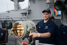 """CORAL SEA (Aug. 8, 2013) Quartermaster Seaman Weston Warr, assigned to the Ticonderoga-class guided-missile cruiser USS Antietam (CG 54), """"flashes"""" a message to the guided-missile destroyer USS Preble (DDG 88) using a search light on the bridge wing. Antietam is on patrol with the George Washington Strike Group in the U.S. 7th Fleet area of responsibility supporting security and stability in the Indo-Asia-Pacific region. (U.S. Navy photo by  Declan Barnes/Released)"""