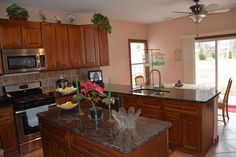 Eat-in kitchen with granite counter tops, stainless steel appliances, and sliding doors to the back yard.