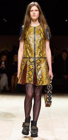 On the Burberry runway – a short pleated dress in contrasting panels of bright, patterned leather, worn with The Buckle Boots in black with gold studs, and The Patchwork, the new one-of-a-kind signature bag