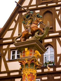 """George's Fountain, Rothenburg ob der Tauben"""" ~ A statue atop a fountain Georgsbrunnen, (St. George slaying the dragon in the walled medieval town of Rothenburg ob der Tauben, Bavaria, Germany. Visit Germany, Germany Travel, Rothenburg Germany, Rothenburg Ob Der Tauber, Romantic Road, Beau Site, Medieval Town, Bavaria Germany, Central Europe"""