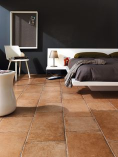 PIN 6: Terracotta floor tiles used in a contemporary bedroom. The tiles make this room look a little industrial but also very natural and earthy.