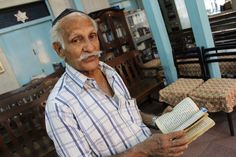Solomon Penkar, the caretaker of Tiferet Israel synagogue, pages through a Psalms book in Marathi, one of India's official languages.
