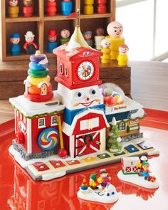 """Department 56 North Pole Village Series """"Fisher-Price™ Fun Factory"""" For more information www.department56.com Shop 24/7 shop.department56.com ©2014 Mattel. All Rights Reserved. Manufactured for and distributed by Department 56, Eden Prairie, MN."""