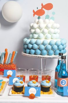 """Goldfish Themed Party: """"We love the simplistic and clean signage and that cake pop cake! Other sweet treats on the dessert table included Goldfish cake pops styled in a blue Sixlet fishbowl {brilliant}, goldfish shaped cookies, pretzel fishing rods with chocolate sea pearls, and Goldfish-topped cupcakes.  There was 'sea water' to wash everything down."""""""