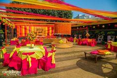 Vibrant pink, orange and yellow decor at the mehendi ceremony.