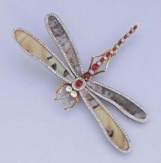//AN ATTRACTIVE ANTIQUE MOSS AGATE, RUBY AND DIAMOND DRAGONFLY BROOCH   The dragonfly with moss agate and diamond bordered wings to the alternating ruby and diamond body and diamond collet eyes, millegrain setting, mounted in platinum and gold, circa 1900, 7.4 cm. long