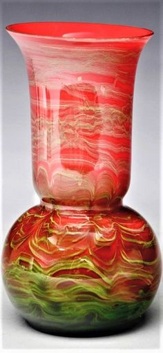 Loetz vase in the Titania decor has round bulbous body leading to cylindrical neck and flared upper rim. Vase is decorated with clear outer layer over a layer of random green metallic threads over an imperial red ground layer.