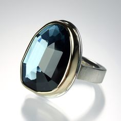 A sterling silver and 14K yellow gold ring with an  asymmetrical faceted London blue topaz on a comfort Y band.  Stone measures .75 x 1.