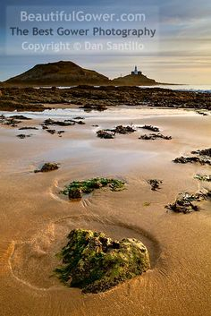 """Bracelet Bay and Mumbles Lighthouse by Dan Santillo. """"The rock with the lovely golden sand around it caught my eye so I placed it in the foreground to emphasise it. It wasn't long after sunrise and the light and cloud colour were still great. Best Vacations, Vacation Destinations, Beautiful World, Beautiful Places, Amazing Places, Places To Travel, Places To See, Island Resort, Island Beach"""