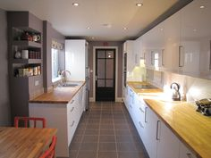 Long white gloss kitchen with small dining area