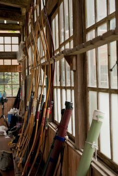 Kyudo equipment. 弓具。 At 弓道場 kyudo-jo, places where kyudo is practiced, the yumi (bow) are placed on a wooden 弓立 (yumi-tate), or bow stand. The colorful tube-like objects are 矢筒 (yadzutsu) or quivers, in English. They can come in different colors, patterns, and lengths according to the length of an archer's arrows.