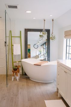 Abrazo bath   Purist bath filler   Ann Sacks floor tile   Thiessen and Smith's shared master bath is modern with a few rustic touches that make it warm and comfortable, like hanging air plants and a bamboo ladder. The wood-look floors are actually easy-care porcelain tile.