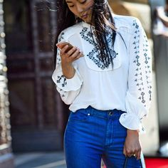 An embroidered high neck blouse worn with light wash denim