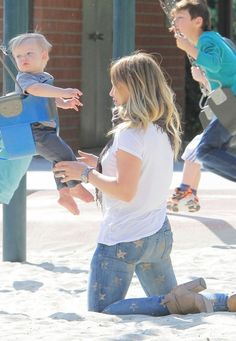 Hilary swinging her son Luca on the swings. :)