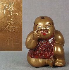 """19c netsuke lacquer boy bekkako by TATSUKE TAKAMASU // golden lacquer netsuke of a sitting boy tugging at his face below his eye with a smiling expression, his tongue sticking out while he is hiding a toy drum / rattle behind his back. This gesture, called Bekkako, is from a child's game and translates as something like """"see my eye"""" while teasing a playmate and inviting him to guess what is hidden behind your back."""