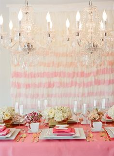 Gorgeous pink tablescape with a ombre feather background, fresh flowers, and chandeliers