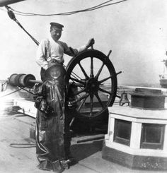 Captain Youngren and daughter at the wheel of the 1874 ship Oriental.