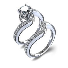This breath taking 14 karat white gold wedding set features an engagement ring with 1/5 carat of round diamonds pave set in a gentle twist around the center stone of your choice and is paired with a matching curved band set with an additional 1/5 carat.