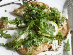 White Pizzas with Arugula: Ina Garten makes fresh pizza dough, then tops it with three creamy cheeses. She finishes it off with arugula, lemon and olive oil when it comes out of the oven.