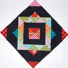 "Quilt block.                                                    I like the use of the black with bright colors but would coordinate the other  ""layered squares"" to appear in gradient colors for depth"