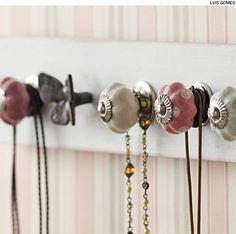 Presos a uma régua de madeira, os puxadores de porcelana compõem um bonito suporte para colares.
