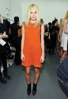 Kate Bosworth in a mod orange shift dress, sleek hair and pointy black ankle boots backstage at Calvin Klein