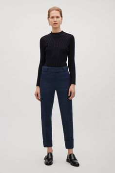 These slim-fit trousers are made from comfortable cotton with modern turn-ups and neat press folds along the front. Designed to sit between the hip and waist, they have a classic hook and bar front fastening, slanted front pockets and welt pockets at the back.