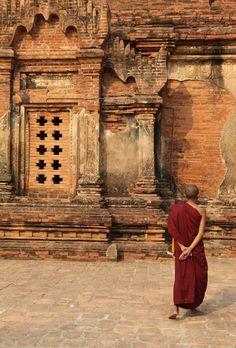 Young monk meditating the teachings of Buddha, facing the ruins of an ancient pagoda in Bagan, Myanmar.
