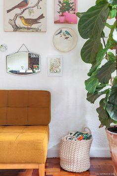 Parede da sala de estar decorada com quadros, pratos e objetos de decoração. Ao lado, uma ficus lyrata traz o verde para dentro de casa.