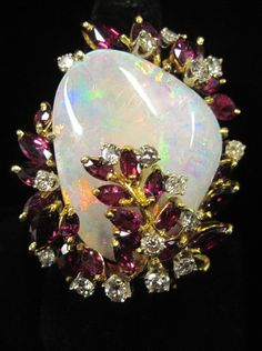 An opal, ruby, diamond and eighteen karat gold ring  centering a polished opal accented by marquise-cut rubies and round brilliants-cut diamonds; total diamond weight approximately: 1.35 carats.