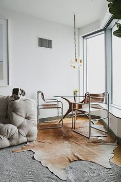 Modern dining nook with metal frame chairs, midcentury glass table, cowhide rug and tufted sofa.
