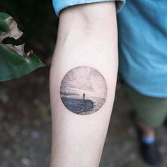 Landscape circle tattoo on the inner forearm.