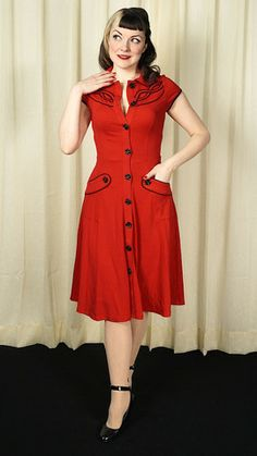 Wavy Pinstripe Western Dress:For our Vixens everywhere. This dress will make you stand out in every crowd. It's the perfect red shirt dress, with Peter Pan collar, black functional rose buttons down the front, pockets, cap sleeves, and pinstriped black embroidery on the shoulders. It fits beautifully, hugs your waist, flares to the hem and swings when you walk. A must have. It's... $80.00
