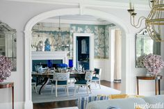 """""""In the dining room, the misty blue background on the custom Gracie wallpaper sets off the sparkle of mirrored panels . . . John Rosselli klismos chairs have seats covered in Garrett Leather with backs in Fortuny's Cimarosa. Curtains in Fortuny's Tapa trimmed with a Samuel & Sons border."""" Interior design by Lee Ann Thornton. Photo: James Merrell. Interview by Barbara King. """"The Timeless Appeal of Blue and White"""" produced by Doretta Sperduto. House Beautiful (September 2014)."""